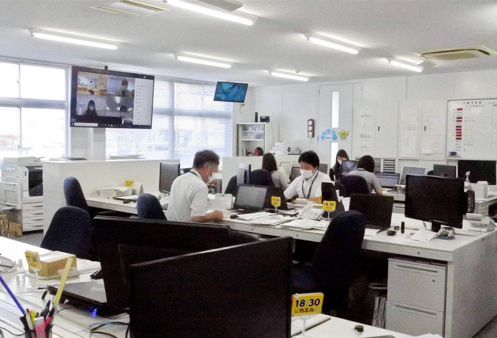 株式会社デンテックスの事務所内部。上部モニターでテレワーク管理を行う